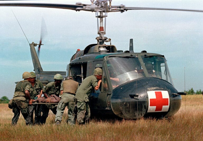 "A wounded member of the 1st Plt. Company ""C,"" 25th Infantry Division, is helped to a waiting UH-1D ""Iroquois"" helicopter in Vietnam, May 10, 1967, during the Vietnam War.  (AP Photo)"